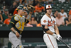 August 22, 2017 - Baltimore, MD, USA - The Baltimore Orioles' Chris Davis, right, strikes out in front of Oakland Athletics catcher Bruce Maxwell to end the game at Oriole Park at Camden Yards in Baltimore on Tuesday, Aug. 22, 2017. The A's won, 6-4. (Credit Image: © Kenneth K. Lam/TNS via ZUMA Wire)