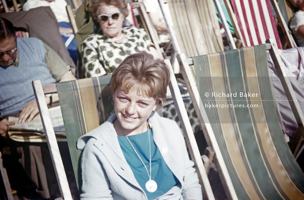 A teenage girl smiles in summer sunshine while sitting on a seafront deckchair in the early nineteen sixties.