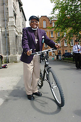 Former Archbishop of Cape Town and Nobel Peace Prize winner, Dr Desmond Tutu sits on a bike borrowed from a student after being made an honorary fellow of the Philosophical Society at Trinity College.