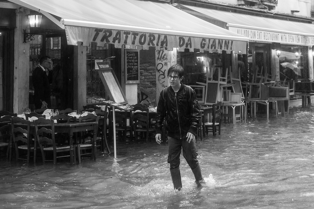Venice, Italy. 29 October, 2018. A boy walks through a flooded street in Cannaregio district on October 29, 2018, in Venice, Italy. This is a selection of pictures of different areas of Venice that the press has not covered, were resident live and every year they have to struggle with the high tide. Due to the exceptional level of the 'acqua alta' or 'High Tide' that reached 156 cm today, Venetian schools and hospitals were closed by the authorities, and citizens were advised against leaving their homes. This level of High Tide has been reached in 1979. © Simone Padovani / Awakening / Alamy Live News