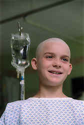 Portrait of young boy with cancer standing next to drip in hospital ward,