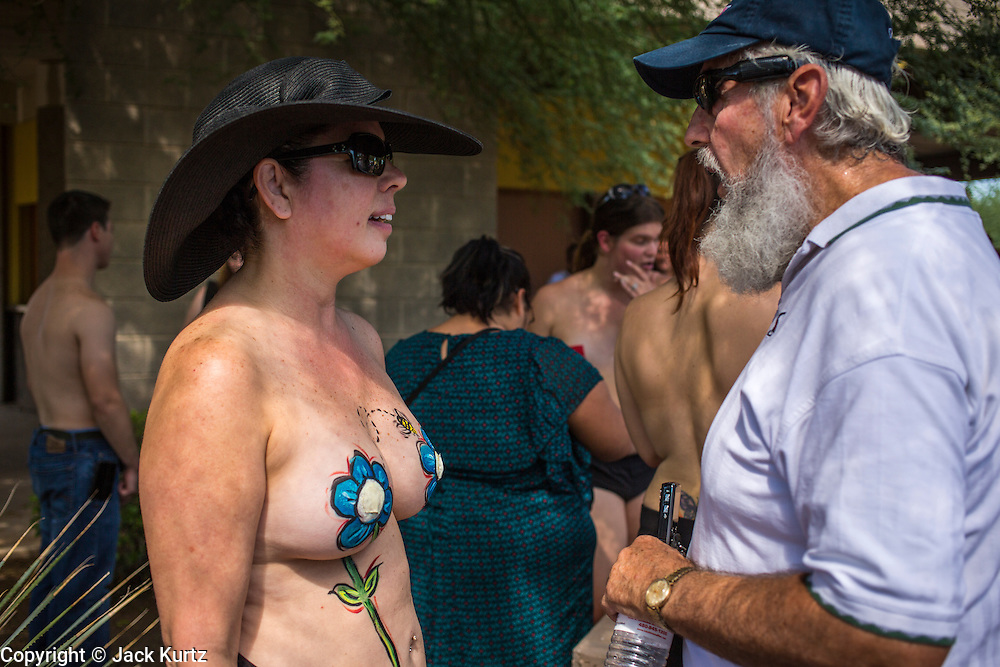 26 MARCH 2012 - PHOENIX, AZ: CHRISTI, a topless protester from Glendale, AZ, talks to a male spectator at the Phoenix topless protest. About 40 people marched through central Phoenix Sunday to call for a constitutional amendment to give women the same right to go shirtless in public that men have. The Phoenix demonstration was a part of a national Topless Day of Protest. Phoenix prohibits women from going topless in public so protesters, women and men, covered their nipples and areolas with tape. The men did it to show solidarity with the women marchers.    PHOTO BY JACK KURTZ