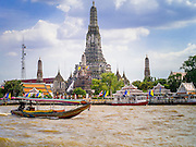 """05 OCTOBER 2012 - BANGKOK, THAILAND:   A long tail boat passes Wat Arun, the """"Temple of the Dawn"""" on the Chao Phraya River. Wat Arun is one of the most famous temple in Thailand. Its Khmer style """"prang"""" dominates the skyline of this part of Bangkok.     PHOTO BY JACK KURTZ"""