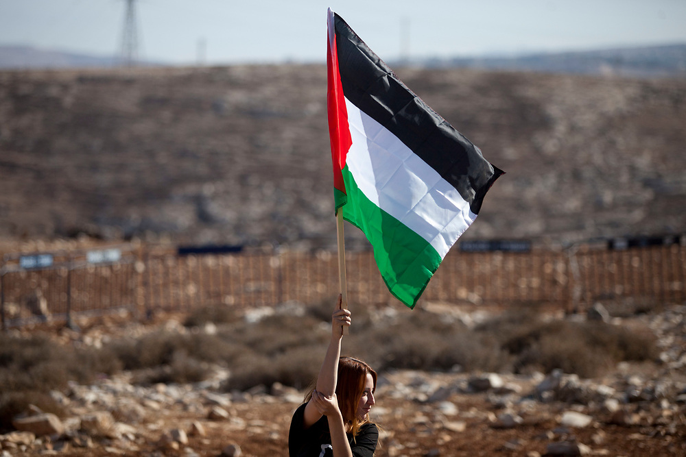 """A left-wing Israeli activist waves Palestine's national flag as she protests against violence by right-wing activists and settlers, during a demonstration held at the entrance to the West Bank settlement of Anatot, near Jerusalem, Israel, on November 11, 2011. Hundreds of pro-Palestinian activists demonstrated following a clash between left-wing activists and the residents of Anatot in September, and a recent series of violent acts under the slogan """"price tag"""", allegdly committed by Jewish settlers."""