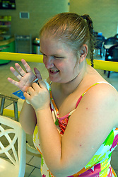 Day service user with learning disability standing at the edge of the local swimming pool,