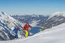 Skiers climbing on snow covered mountain