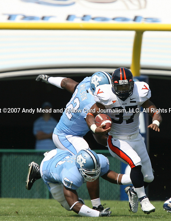 15 September 2007: Virginia's Cedric Peerman (37) gets past North Carolina's E.J. Wilson (92) and Wesley Flagg (below). The University of Virginia Cavaliers defeated the University of North Carolina Tar Heels 22-20 at Kenan Stadium in Chapel Hill, North Carolina in an Atlantic Coast Conference NCAA College Football Division I game.