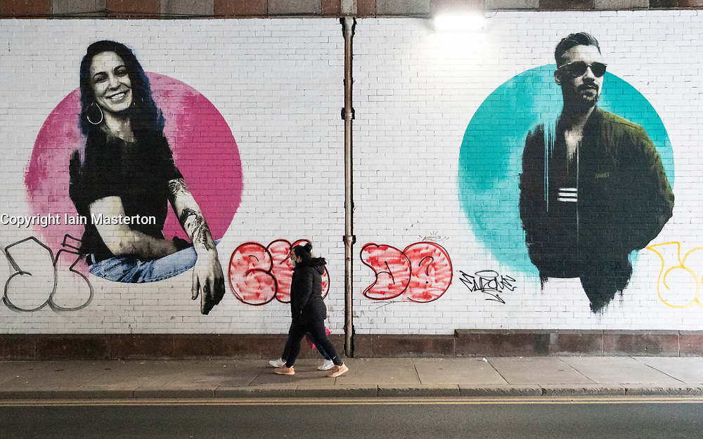 Glasgow, Scotland, UK. 6 Mar 2021. With Scotland remaining under national lockdown during the covid-19 pandemic Glasgow city centre remains a virtual ghost town with few people in the city centre and almost all shops and businesses still closed.  Pic; Couple walk past large murals in the city centre. Iain Masterton/Alamy Live News