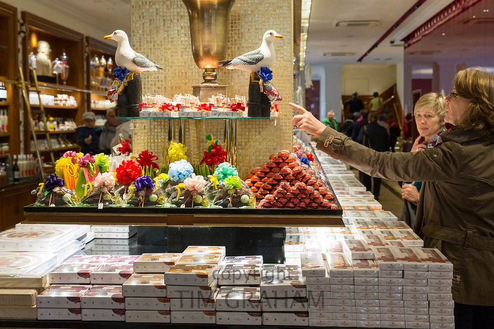 Marzipan sweets and candy on display and shoppers inside J.G. Niederegger shop in Lubeck - famous for marzipan, Germany