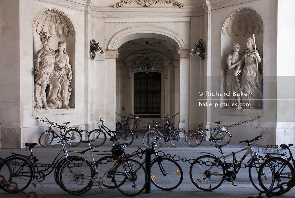 Bikes are locked up on railings beneath Romanesque figures in the Hofburg Kaiserappartements, on 28th June 2016 in Vienna, Austria. Hofburg Palace is the former imperial palace forming part of the official residence and workplace of the President of Austria. Built in the 13th century and expanded in the centuries since, the palace has housed some of the most powerful people in European and Austrian history, including monarchs of the Habsburg dynasty, rulers of the Austro-Hungarian Empire. (Photo by Richard Baker / In Pictures via Getty Images)
