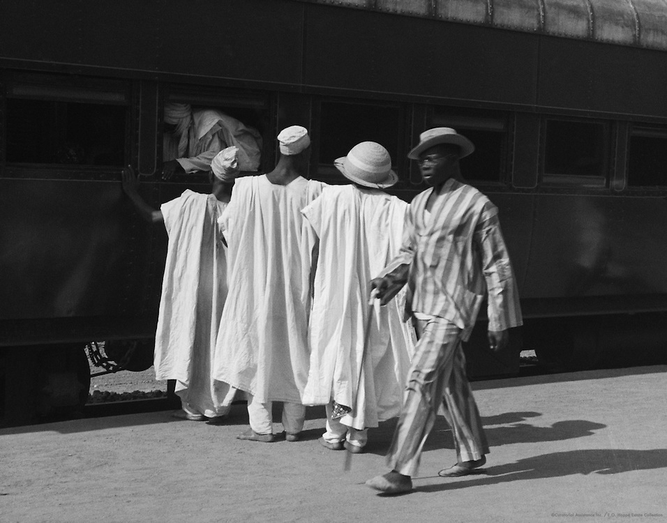 Man in Modern Suit Passing Men in Traditional Robes at Railway Station, Lagos, Nigeria, Africa, 1937