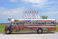 MR photo of six professional Panamanian dancers  from the Panama National Ballet,  balancing on top of a classical ¨Red Devil¨bus, a colorful expression of folk art, now disapearing after the new transportations systems are being implemented.