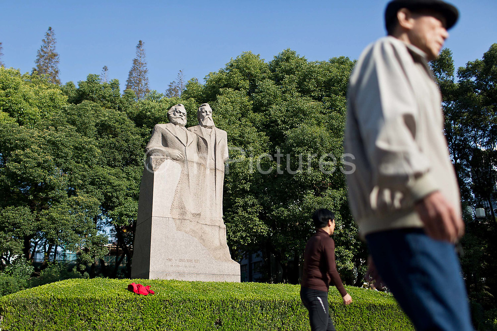 People relax in front of a statue of Marx and Engles at Fuxin Park in Shanghai, China on 15 November, 2013.