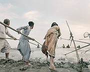 """Local Muslim men stand on the rim with nets attached to long poles and try to be the first one to catch the coconuts that have been thrown in the cold mud by pilgrims. They collect the coconuts and will either sell them back to newcomer pilgrims, resale it in the market or keep it for themselves. The steep trek to the rim of the highest volcano is the first ritual of the Hinglaj pilgrimage. Pilgrims come up to throw a coconut in the cold mud (to thank the gods for granting their wish) and to apply the holy mud to their faces etc. The area around Chandragup (meaning """"Moon Well""""), a sacred site to Hindu of 3 mud volcanoes (mainland Asia's largest ones)."""