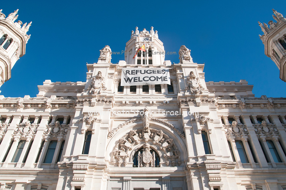 Refugees Welcome banner draped across the facade of the Palacio de Cibeles, City Hall, Madrid, Spain