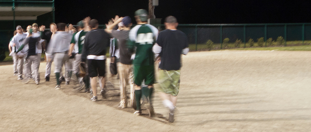 recreation baseball players congratulate their opponents with high fives after their night game at Lions Field in Bremerton, Kitsap County, Washington, USA motion blur expresses movement in this panorama.