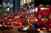 Scene as buses and cars move along Camomile Street in the City of London in the early evening as nigh falls around 4pm in the Winter. The red rear lights of the vehicles reflect around the scene giving it a red tinge to match the colour of the London bus.