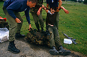 A boy soldier has collapsed on the ground suffering from fatigue and dehydration on a rigorous march conducted as a squad of soldier recruits, over undulating terrain with each candidate carrying a bergen (back pack) weighing 35 pounds (plus water) and a weapon. Two senior trainers haul the buy up who fell under the weight of his backpack and weapon carried on a hot day and without drinking enough fluids. The 10-mile march must be completed in 1 hour and 50 minutes and it forms part of the 14-week long Pegasus (P) Company selection programme that recruits wanting to join the British Army's elite Parachute Regiment, held regularly at Catterick army barracks in Yorkshire, need to pass (with other tests) before earning the right to wear the esteemed maroon beret.