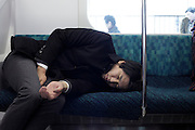 deep sleeping businessman during his train commuting Japan Tokyo