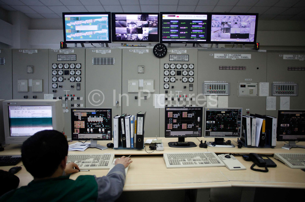 Workers monitor gauges and sensors in a control room at a small power plant in Changshu, Jiangsu Province, China on 18 March, 2011.  China is quickly pushing to expand its alternative energy options while currently a majority of its rapidly expanding appetite for electricity is satisfied by coal, which the country has an abundant supply of.