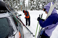 Two young women next to a car with cross country skis preparing to go nordic skiing in Bend, Oregon. (releasecode: jk_mr1033, jk_mr1032) (Model Released)