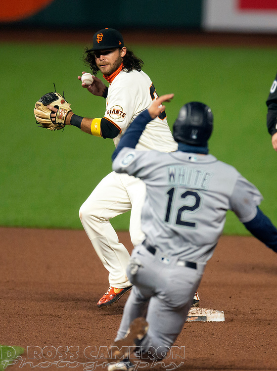 Sep 16, 2020; San Francisco, CA, USA; San Francisco Giants shortstop Brandon Crawford (35) prepares to throw on to first base over Seattle Mariners first baseman Evan White (12) to complete a double play during the eighth inning of a baseball game at Oracle Park. Pinch hitter José Marmolejos (26) was out at first base. Mandatory Credit: D. Ross Cameron-USA TODAY Sports