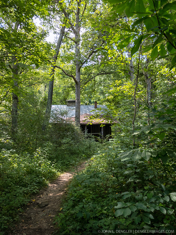 """An abandoned log cabin sits in the woods near Pulltite Spring along the Current River, one of two rivers that make up the Ozark National Scenic Riverways in Missouri. The cabin (note the vertical log construction) was built as a """"retreat"""" for early 20th century visitors who came to float the Current River. The Current River is the most spring-fed of all the rivers in the Missouri Ozarks. The river is a favorite with paddlers who enjoy the cold crystal clear water from springs that feed the Current River, including Cave Spring, Pulltite Spring, Round Spring, Blue Spring, and Big Spring. The scenic river is lined with rock ledges, caves, gravel bars and bluffs.<br /> <br /> The Ozark National Scenic Riverways was established in 1964, making it America's first national park area to protect a wild river system. The Ozark National Scenic Riverways, which include the Current and Jacks Fork rivers, is known for its caves, springs, sinkholes and losing streams. Visitors can enjoy water activities, such as floating, canoeing, tubing, swimming, and fishing. Additionally, there are opportunities for hiking, horseback riding, and wildlife viewing. Over 130 miles of waterways and 300 identified caves exist within the park."""