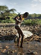 Isak washing in a stream. At the Hadza camp of Dedauko.