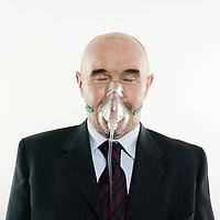 senior man portrait studio wearing oxygen mask