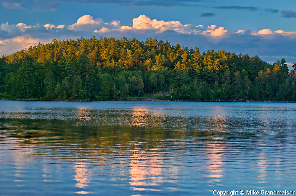 Clouds reflected in Snake Island Lake at sunset.  The White Bear Forest Conservation Reserve<br />Temagami<br />Ontario<br />Canada