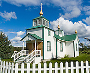 """The Russian Orthodox Church in the town of Ninilchik was redesigned and constructed in 1901 in Alaska, USA. Notice that the Russian Orthodox Cross has two extra arms: the top arm represents the inscribed acronyms [ INRI in Latin,  in Greek, and a Hebrew version, meaning """"Jesus the Nazarene, King of the Jews"""" ], and the angled bottom arm is his footrest. Russian Orthodox religion was born in Kiev in the """"land of the Rus"""" in 988 AD as a branch of Eastern Orthodox Christianity. After Russian discovery of Alaska and the Aleutian Islands in 1741, Russian fur traders taught Christianity to Alaskan Natives. The first eight Russian Orthodox missionaries came to Kodiak Island, Alaska (Russian America) in 1794. The religion spread amongst Alaskans, and the monks mission was made a diocese of the Russian Orthodox Church a few years after the United States purchased Alaska from Russia in 1867. Ninilchik is on the Sterling Highway on the west side of the Kenai Peninsula on the coast of Cook Inlet, 186 miles by road from Anchorage and 38 miles from Homer. The Alaska Native Claims Settlement Act recognized Ninilchik as an Alaska Native village. Ninilchik hosts the annual Kenai Peninsula State Fair."""