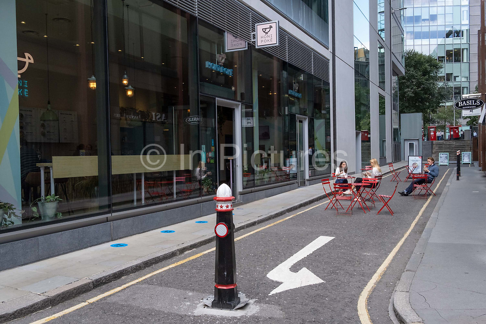 In the week that schools open again, City workers still largely remain working from home during the Coronavirus pandemic and a few tables for those who have commuted in can eat lunch on closed streets in the Square Mile, the capital's financial district, on 1st September 2020, in London, England.