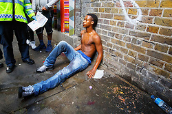 © Licensed to London News Pictures. 29/08/2016. London, UK. A drunk man is being helped by people on the second day of Notting Hill Carnival in west London, Monday 29 August 2016. Photo credit: Tolga Akmen/LNP