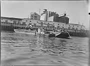 """9904-B01C. """"NW Electrical Co. cable being laid across harbor. Ed Hargrave's tug. September 30, 1948"""" caption published in Oregonian September 30, 1948 pg. 11 """"High Voltage Cable Laid Across Harbor Floor. Barge carrying reel and 1,000-volt submarine cable which Pacific Power & Light company laid across the Willamette River between the Albina Fireboat Station and crown Mills Wednesday to supplement its connections between Albina and Pittock stations."""" (A was published)"""