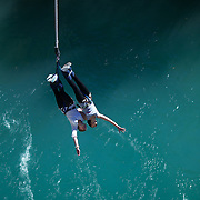 Two girls tandem bungy jump from The AJ Hackett Kawarau Bridge Bungy Jump, Queenstown New Zealand. The Kawarau Bridge Bungy jump was the World's first Commercial bungy Jump and opened in 1988. The 43m jump attracts tens of thousands of bungy jumpers each year. Queenstown, Central Otago, South Island, New Zealand. 30th March 2011. Photo Tim Clayton