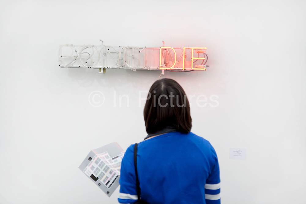 Die. A neon artwork entitled 'Produce, Consume' Die'. Visitors and exhibitors at the many galleries exhibiting at the Frieze Art Fair 2010. This art fair is for work at the high end of international contemporary art with many well known artists on show from many of the world's most reknowned dealers.