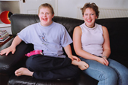 Teenage boy with Downs Syndrome sitting on sofa in living room next to sister,