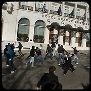 Teenage protestors against riot police in front of Hotel Grande Bretagne in Syntagma square, Athens. Following the murder of a 15 year old boy, Alexandros Grigoropoulos, by a policeman on 6 December 2008 widespread riots, protests and unrest followed lasting for several weeks and spreading beyond the capital and even overseas<br /> <br /> When I walked in the streets of my town the day after the riots I instantly forgot the image I had about Athens, that of a bustling, peaceful, energetic metropolis and in my mind came the old photographs from WWII, the civil war and the students uprising against the dictatorship. <br /> <br /> Thus I decided not to turn my digital camera straight to the destroyed buildings but to photograph through an old camera that worked as a filter, a barrier between me and the city.