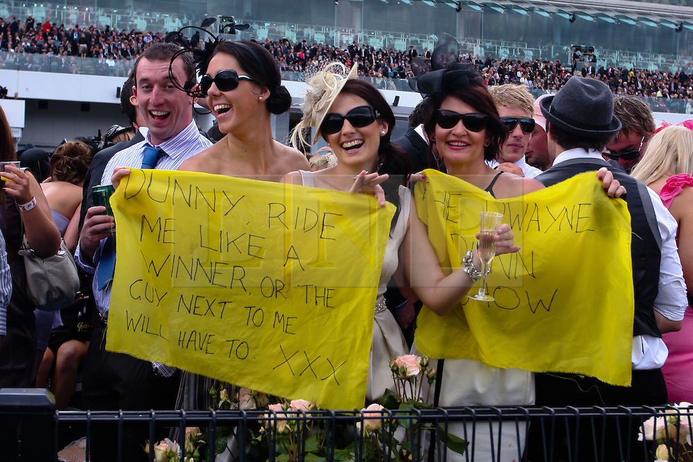 (c) under License to London News Pictures 02/11/2010. Racegoers sending a message to a jockey racing in the 2010 Melbourne Cup