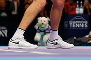 Hattie the balldog with a ball in her mouth framed in between Greg Rusedski's legs.<br /> Ball dogs step onto the court at the Royal Albert Hall for the first time in UK history during this year's Champions Tennis event in association with Skinner's Pet Food, with dogs provided by Canine Partners. <br /> During the Champions Tennis match at the Royal Albert Hall, London, United Kingdom on 6 December 2018. Picture by Ian Stephen.