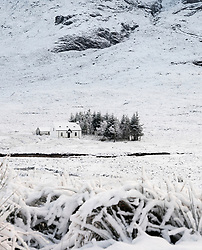Snow covered winter landscape and cottage in Glen Coe in Scottish Highlands, Scotland, UK