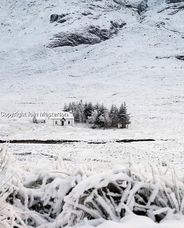 Snow covered winter landscape and cottage in Glen Coe in Scottish Highlands, Scotland, UK