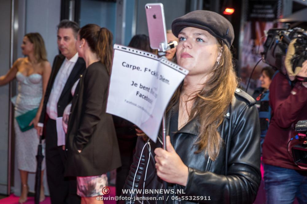 "NLD/Amsterdam/20170911 - Première Bella Donna's, meisje met bord "" je bent live op Facebook"""