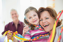 Family with blowout paper streamer at birthday party, smiling