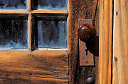 Detail of wood door with glass panes and marble door knob, Bodie State Historic Park (National Historic Landmark), California