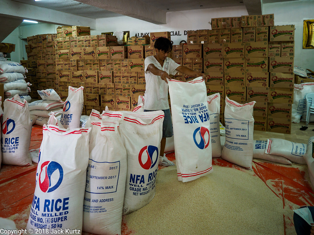 """22 JANUARY 2018 - LEGAZPI, ALBAY, PHILIPPINES:  A worker at the Albay Provincial Social Welfare and Development Office package emergency food supplies to be delivered to the evacuees from the Mayon volcano eruptions. There were a series of eruptions on the Mayon volcano near Legazpi Monday. The eruptions started Sunday night and continued through the day. At about midday the volcano sent a plume of ash and smoke towering over Camalig, the largest municipality near the volcano. The Philippine Institute of Volcanology and Seismology (PHIVOLCS) extended the six kilometer danger zone to eight kilometers and raised the alert level from three to four. This is the first time the alert level has been at four since 2009. A level four alert means a """"Hazardous Eruption is Imminent"""" and there is """"intense unrest"""" in the volcano. The Mayon volcano is the most active volcano in the Philippines. Sunday and Monday's eruptions caused ash falls in several communities but there were no known injuries.   PHOTO BY JACK KURTZ"""