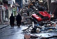 Two policemen walk near earthquake debris in Golcuk, Turkey. August. 1999.