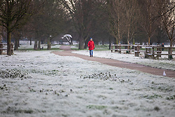 © Licensed to London News Pictures. 25/12/2018. Cambridge, UK. A woman walking on Stourbridge Common by the River Cam in Cambridge after a heavy frost on Christmas morning. Photo credit: Rob Pinney/LNP
