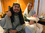 Garden City, New York, USA. December 6, 2013. Visitors experience the nativity scene at the manger, with Mary, Joseph, and baby Jesus, the Holy Family, at A Night in Bethlehem, an annual Advent at the Lutheran Church of the Resurrection, on Long Island, on December 6, 7, and 8.