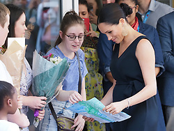 The Duchess of Sussex greets some well wishers with a group hug as she departs from the mothers2mothers charity building in Cape Town. <br />